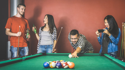 Young friends talking and playing pool at billiard table saloon - Happy friendship concept with fashion people having fun together and drinking beer at snooker gameroom - Vintage retro contrast filter