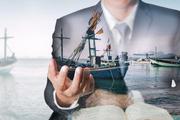 Double exposure of businessman hand hold, fishing boat and sea as business, control and industry concept.
