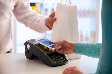 Wireless payment using smartphone and NFC technology. Close up. Customer paying with smart phone in pharmacy. Close Up shopping