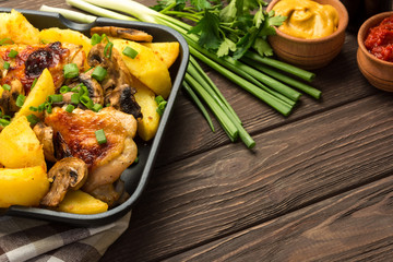 Dinner with baked chicken legs with olives spiced with aromatic herbs and potatoes with mushrooms on a rustic background.  Copy space.