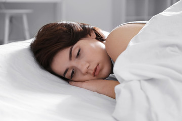 Depressed young woman lying in bed at home, closeup