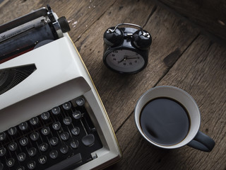 top view photo of vintage typewriter with cup of coffee, on wooden table. retro filtered image