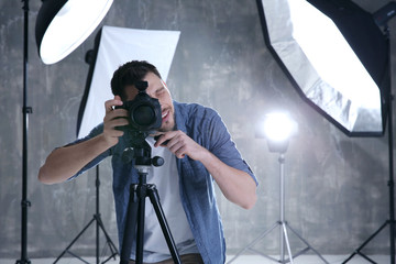 Young male photographer in studio with professional lighting equipment