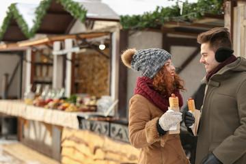Cute couple having lunch break on winter market