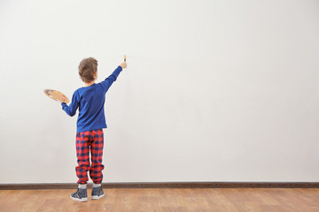 Cute little boy painting on wall in empty room