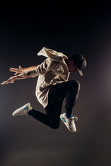 Jumping young male dancer on grey background