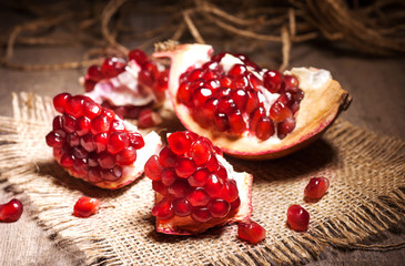 Fresh peeled pomegranates with ruby red beans on old wooden table