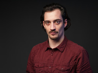 Portrait of a serious man in a burrord shirt, dark gray background