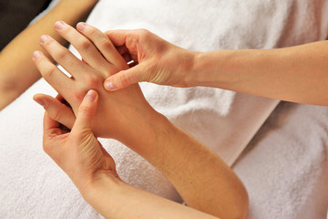Hand massage with white towel, spa salon