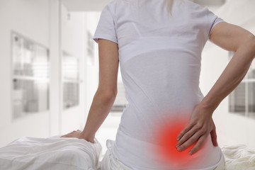 Woman suffering from back pain at home in the bedroom. Uncomfortable mattress and pillow causes back pain.