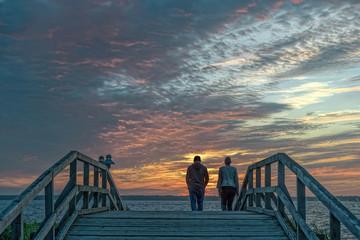 Silhouette von Paar auf Holzbrücke bei Abendrot am Steinhuder Meer