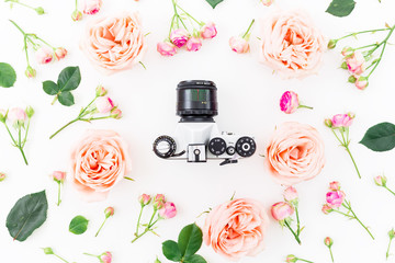 Old Camera and pink roses on white background. Flat lay, Top view