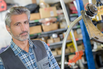 Portrait of mechanic in front of strimmer