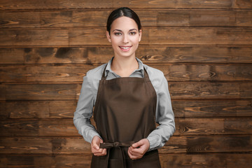 Young woman in apron standing on wooden background