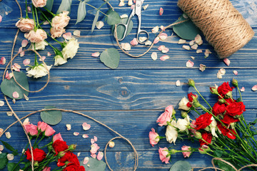 Beautiful roses with thread and scissors on table