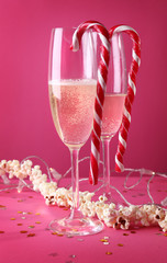 Glasses of champagne with candies on pink background