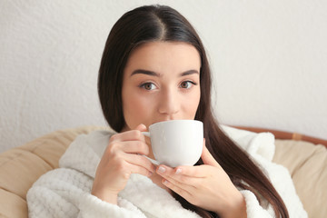 Beautiful young woman drinking coffee in spa salon