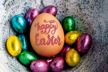 Happy Easter 2017 lettering on egg lined with small chocolate eggs wrapped in colorful foil.