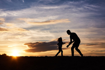 father and his daughter playing on the beach at the sunset time. Happy evening