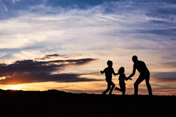 Father and children on the beach at the sunset time. Concept of friendly family.