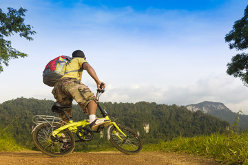 Man asian backpack riding his bike and background of cliff and mountain
