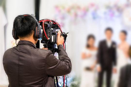 professional videographer recording wedding ceremony day