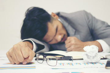 Businessman sleeping at his desk working over a laptop on background after he work all day all night, Tried overworked, Keep fighting in business concept.