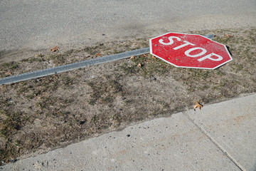 stop sign fallen on the road side