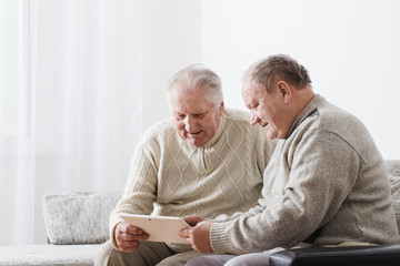 Two elderly men with tablet
