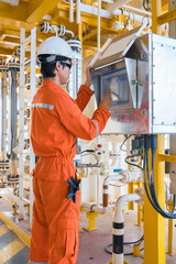 Offshore oil rig worker, Production operator operate valve by using touch screen panel to command open and close valve at oil and gas remote platform.