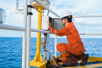 Electrical and Instrument Technician is inspection on lighting of navigation aid system at oil and gas wellhead remote platform, Inspector work.