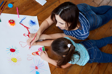 young mother teaches her daughter to draw