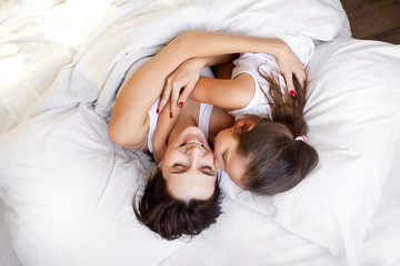 mom and little daughter in bed at home
