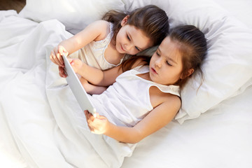 children play in the tablet in bed