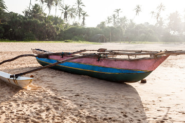 Traditional fishing boat on beach at sunrise