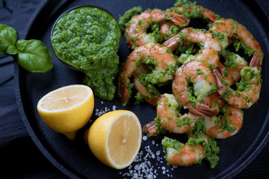 Close-up of a metal plate with tiger shrimps in chimichurri sauce, studio shot