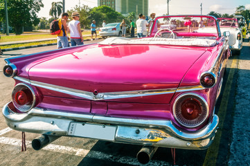 Havana, Cuba -March 14, 2016 - Back detail of a bright colored vintage classic American car parked near Revolution Square, Cuba.