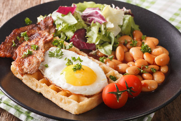 Savory breakfast: waffles with egg, bacon, beans and fresh salad close-up. Horizontal