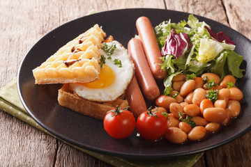 Healthy breakfast: waffle sandwich with egg, sausages, beans and salad close-up. horizontal
