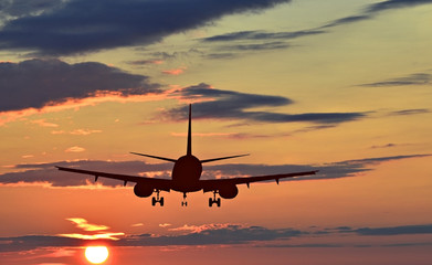 Silhouette of landing airplane at dawn