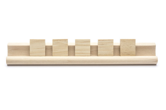 Five blank scrabble tiles on a wooden rack, on white background