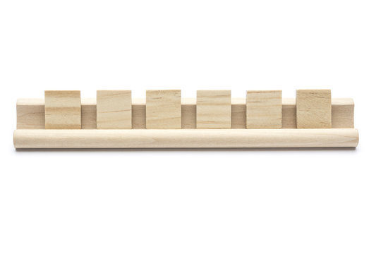Six blank scrabble tiles on a wooden rack, on white background