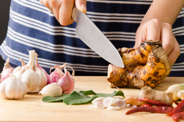Woman cutting galangal on wooden board prepare for cooking Thai food