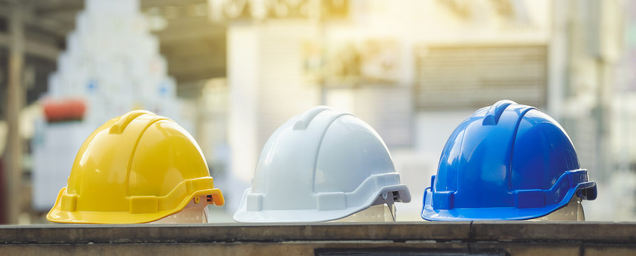 white, yellow and blue hard safety helmet hat for safety project of workman as engineer or worker, on concrete floor on city