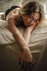 Beautiful blond girl in sexy lingerie posing on bed