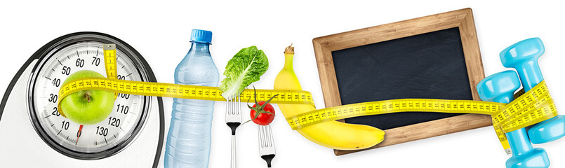 measuring tape  water bottle green apple banana dumbbell and empty slate  blackboard on white bathroom scale fitness concept panorama background / fitness waage maßband apfel tafel konzept hintergrund