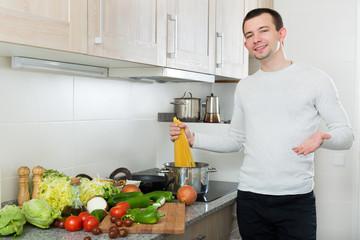 Handsome man cooks spaghetti