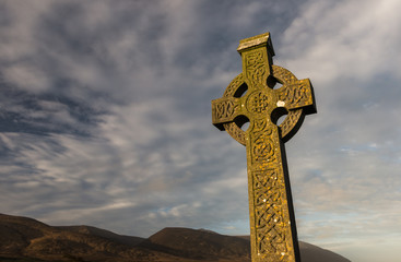 Sunlight hitting celtic cross gravestone at dawn  in rural County Kerry, Ireland
