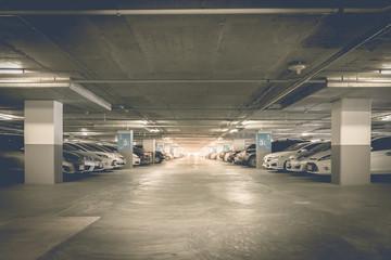 Many cars in parking garage interior, industrial building. Vintage filter effect.