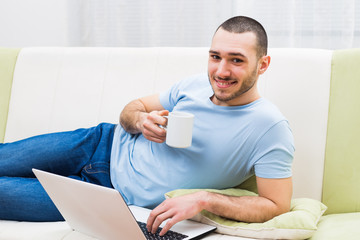 Young man using laptop and drinking coffee at his home.